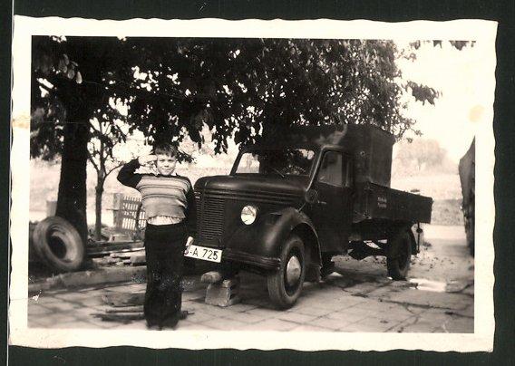 Fotografie Lastwagen, Knabe salutiert vor LKW-Pritsche