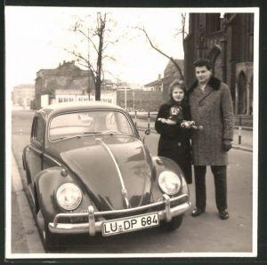 Fotografie Auto VW Käfer, junge Frau mit Kuscheltier neben Volkswagen stehend