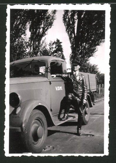 Fotografie Lastwagen - Pritsche, Kraftfahrer mit Ledermantel lehnt am LKW, V.D.M.