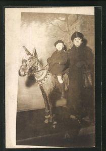Foto-AK Frau und Knabe posieren mit Esel in einer Studiokulisse