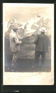 Foto-AK Studiokulisse, zwei Herren vor einer Gebirgsleinwand