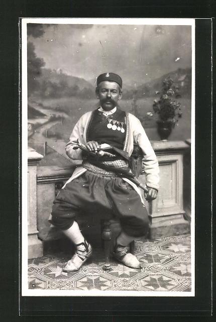 Foto-AK Mann mit Orden und Waffe in jugoslawischer Tracht, Studiokulisse