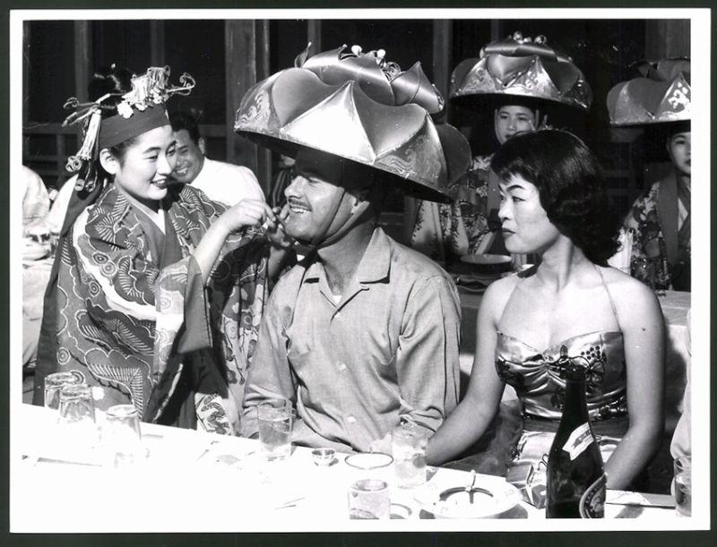 Fotografie Japan, japanische Damen setzen Amerikaner Trachten-Hut auf