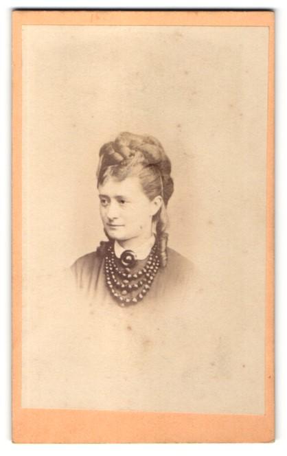 Fotografie L. Bresslmair, Meran, Portrait elegante Dame mit Hochsteckfrisur mit Perlenkette