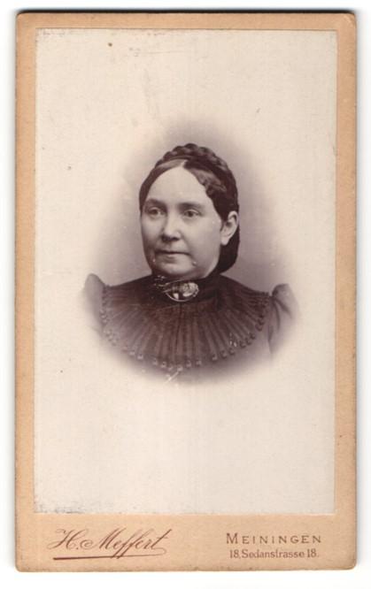 Fotografie H. Meffert, Meiningen, Portrait dunkelhaarige Frau mit Flechtfrisur und Brosche am Kragen