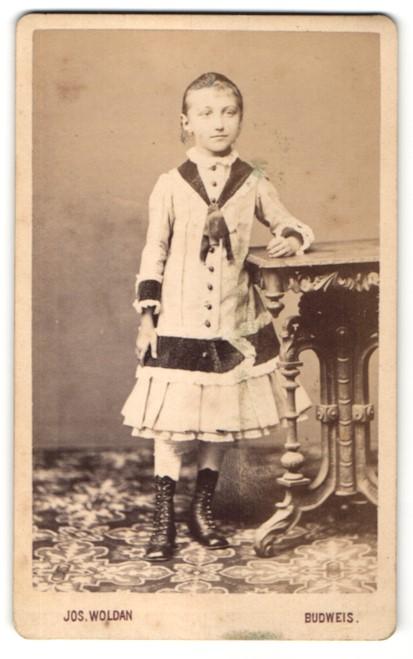 Fotografie Jos. Woldan, Budweis, Portrait bezaubernd süsses Mädchen im hübschen Kleid und Schnürstiefeln