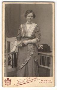 Fotografie Karl Posselt, Ried / Innkreis, Portrait lächelndes Fräulein in elegant besticktem Kleid mit Blume