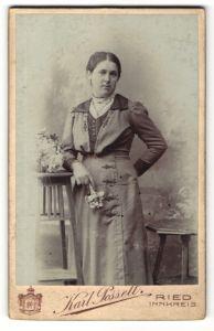 Fotografie Karl Posselt, Ried / Innkreis, charmant blickende Dame im elegant besticktem Kleid mit Blume in der Hand