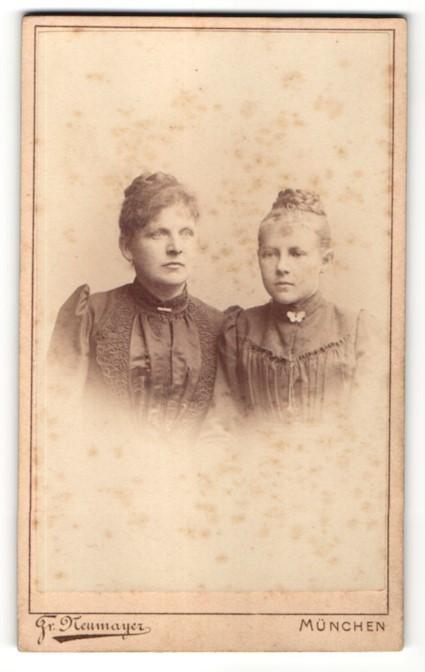 Fotografie Fr. Neumayer, München, Portrait zwei wunderschöne junge Damen mit Flechtfrisuren und Broschen am Kragen