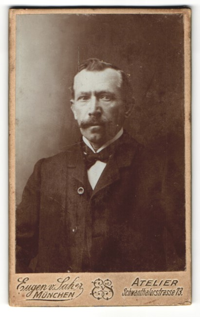 Fotografie Eugen v. Saher, München, Portrait charmanter stattlicher Herr mit Schnurrbart und Fliege im Jackett