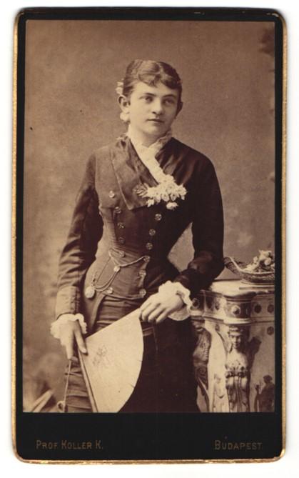 Fotografie Prof. K. Koller, Budapest, Portrait dunkelhaarige junge Schönheit mit Ansteckblume und Fächer