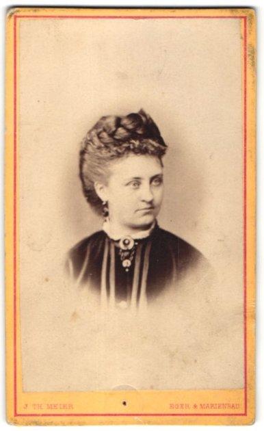 Fotografie J. Th. Meier, Eger & Marienbad, Portrait Frau mit Flechtfrisur und Kragenbrosche im Samtkleid