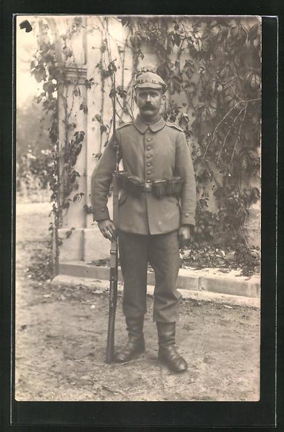 Foto-AK Soldat in Feldgrau mit Artillerie-Pickelhaube mit Überzug