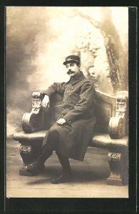 AK Französischer Soldat der Infanterie auf einer Bank sitzend