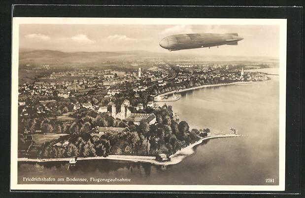 AK Friedrichshafen a. Bodensee, Zeppelin über dem Ort, Fliegeraufnahme