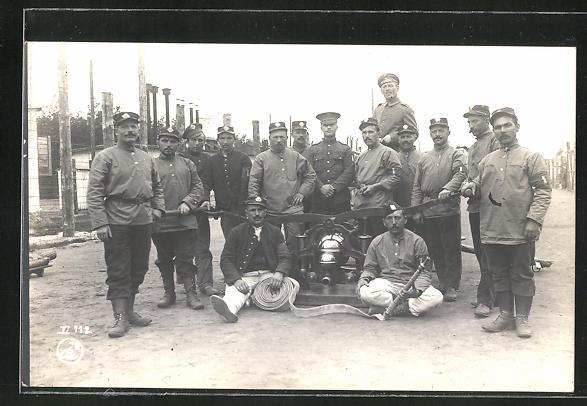 AK Kriegsgefangene stehen um eine Feuerwehrpumpe