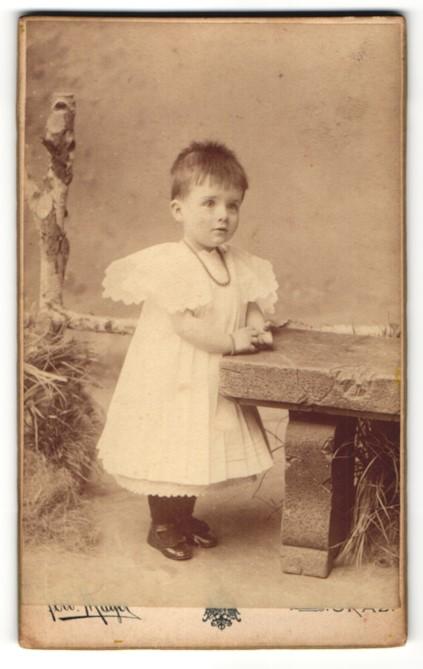 Fotografie Ferd. Mayer, Graz, Portrait kleines Mädchen mit Halskette im weissen Spitzenkleid