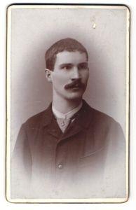 Fotografie Würthle & Spinnhirn, Salzburg, Portrait Mann mit Schnurrbart und Krawatte in winterlicher Jacke