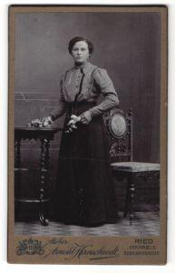 Fotografie Arnold Hirnschrodt, Ried, Portrait Frau in bürgerlicher Kleidung mit Blumen