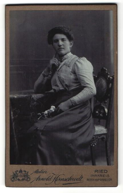 Fotografie Arnold Hirnschrodt, Ried, Portrait Frau in zeitgenössischer Kleidung auf einem Stuhl mit Blumen