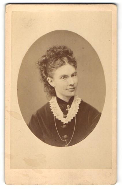 Fotografie B. Johannes, Partenkirchen, Portrait Frau mit Hochsteckfrisur und Spitzenkragen im Samtkleid