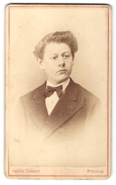 Fotografie Julius Loesch, Freising, Portrait junger Mann mit Fliege im Anzug