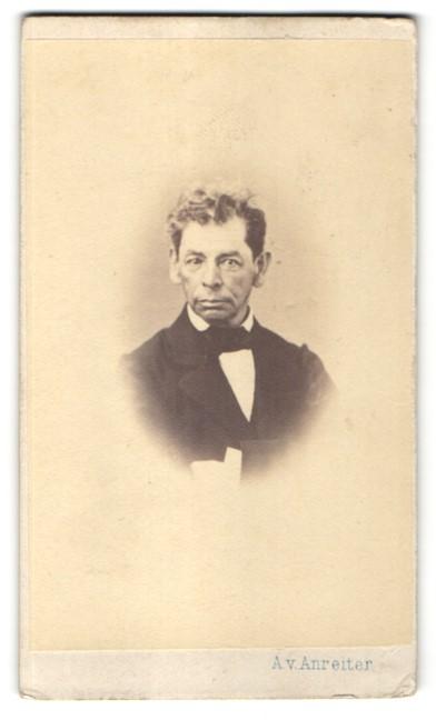Fotografie A. v. Anreiter, Wien, Portrait Mann mit Fliege im Anzug