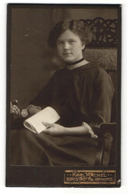 Fotografie Karl Mäckel, Burgstädt i / Sa., Portrait Mädchen in zeitgenössischem Kleid mit Papier auf einem Stuhl