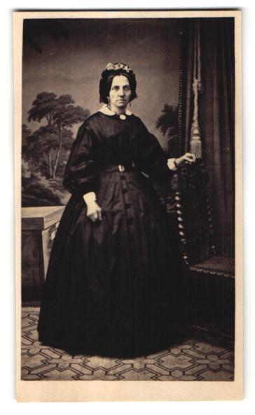 Fotografie Fotograf & Ort unbekannt, charmante ältere Dame mit Rüschenhaube im prachtvollen schwarzen Kleid