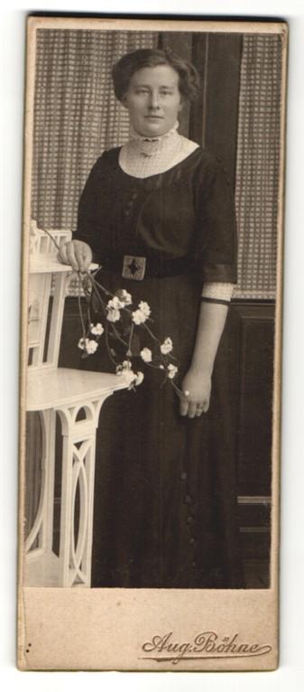Fotografie Aug. Böhne, Bockenem, Portrait charmant blickende junge Frau mit Blume in der Hand