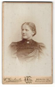Fotografie C. Günteritz, Berlin W., Portrait junge Frau mit Kragenbrosche im Kleid mit Puffärmeln