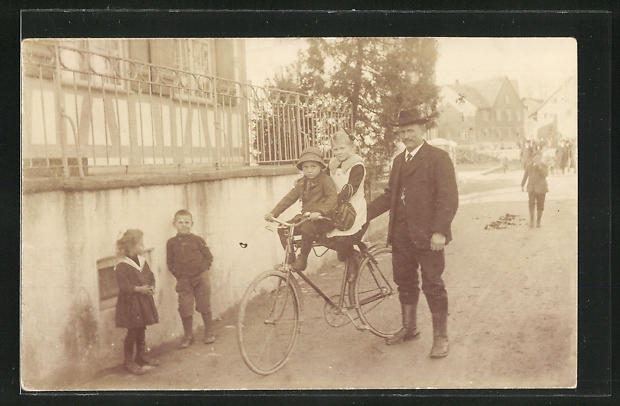Foto-AK Mann schiebt zwei Kinder auf seinem Fahrrad über die Strasse