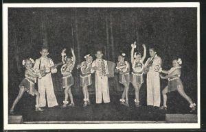 AK Liliputaner musizieren auf der Bühne, Liliputaner-Frauen tanzen dazu in Hawaii-Kostümen