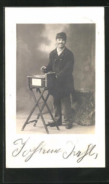 Foto-AK Mann in Mantel und Mütze vor einem Poliphone