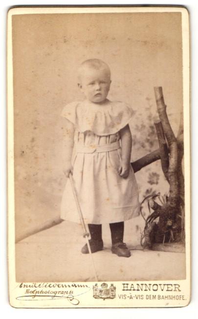 Fotografie Emile Tiedemann, Hannover, Portrait Kleinkind mit geschorenem Haar in Kleidchen