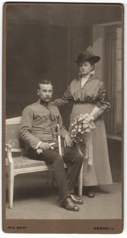 Fotografie M.K. Bett, Krems a. D., österreichischer Soldat in Uniform mit Säbel und Gattin im Foto-Atelier 0
