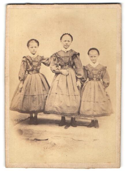Fotografie drei Mädchen in identischen Kleidern, Schwestern 0