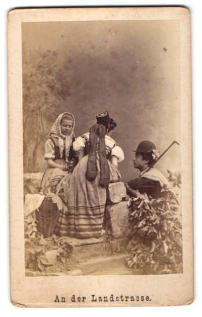Fotografie An der Landstrasse, junger Mann und zwei Maiden in Tracht, Studiokulisse 0