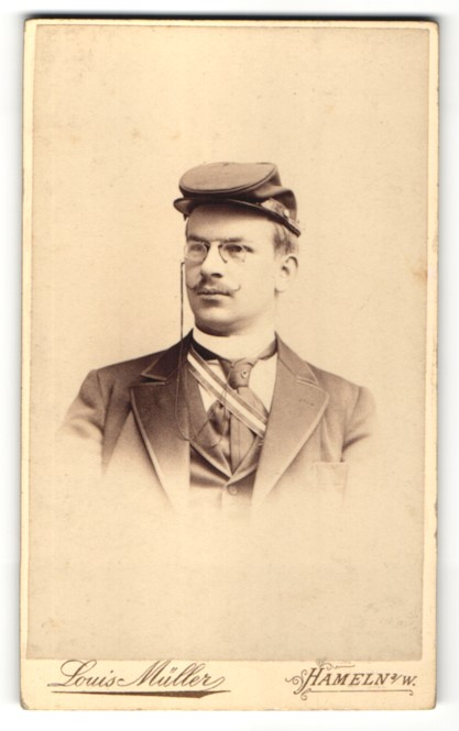 Fotografie Louis Müller, Hameln a/W, Portrait Burschenschaftler mit Mütze und Schärpe, Student 0
