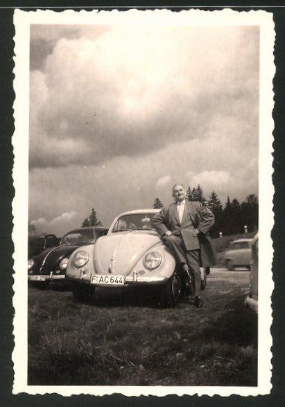 Fotografie Auto VW Käfer, stolzer Fahrer lehnt am Kotflügel seines Volkswagen