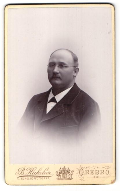 Fotografie Bl Hakelier, Örebro, Portrait Mann mit Brille und Fliege im Anzug 0