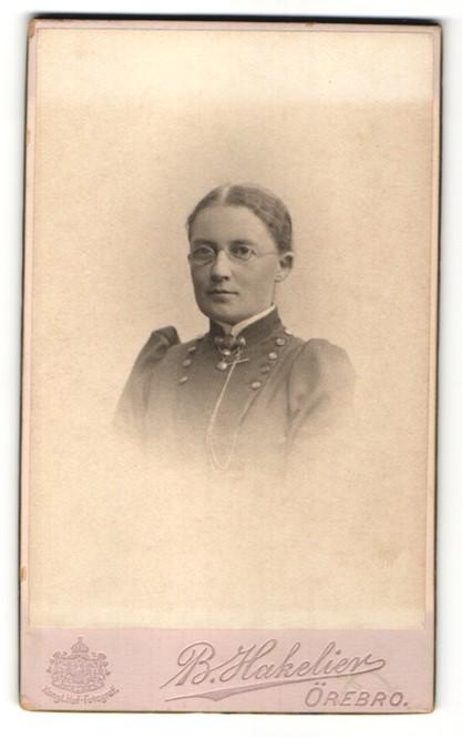 Fotografie B. Hakelier, Örebro, Portrait Frau mit Brille in zeitgenössischem Kleid