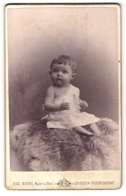 Fotografie Osc. Rothe, Dresden-Friedrichstadt, Portrait Kleinkind im weissen Kleid auf einem Fell