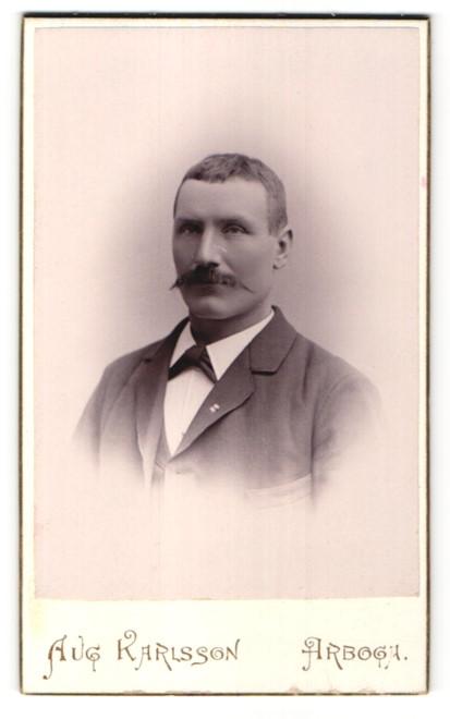 Fotografie Aug. Karlsson, Arboga, Portrait Mann mit Schnauzbart im Anzug