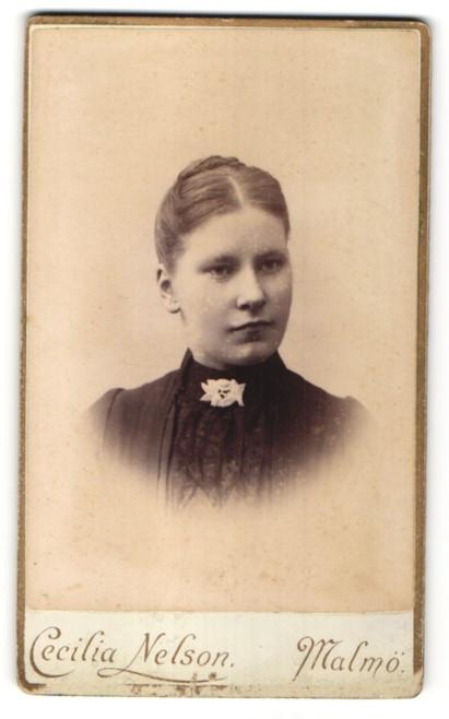 Fotografie Cecilia Nelson, Malmö, Portrait junge Frau mit Kragenbrosche und zurückgebundenem Haar 0