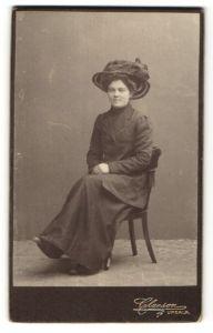 Fotografie Claeson, Upsala, Portrait Frau mit Hut in zeitgenössischer Kleidung auf einem Stuhl
