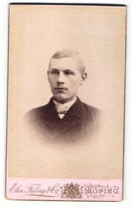 Fotografie Elin Friberg & Co., Köping, Portrait Mann mit Fliege im Mantel
