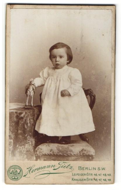 Fotografie Hermann Tietz, Berlin, Portrait Mädchen im weissen Kleid mit Spielzeugpferd 0