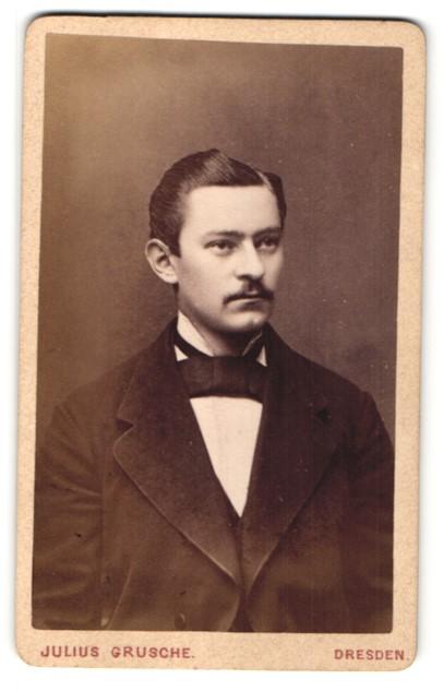 Fotografie Julius Grusche, Dresden, Portrait Mann mit Fliege und Schnurrbart im Anzug 0