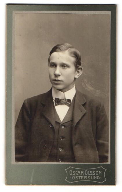 Fotografie Oscar Olsson, Östersund, Portrait Junge mit Fliege im Anzug